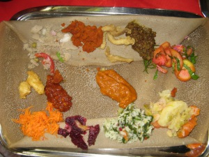 It tastes better than it looks. And yes you eat with your fingers. The injera bread is used as plate and cutlery.